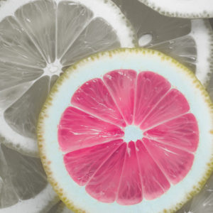 image of sliced pink lemon with yellow lemons